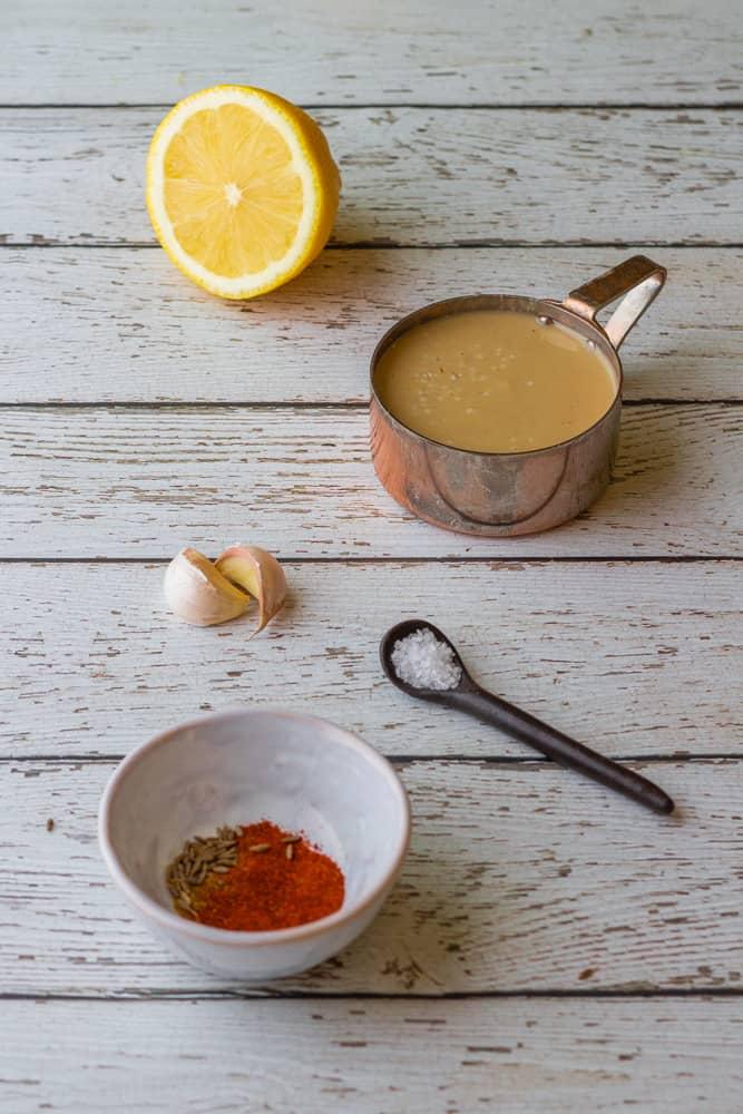 mediterranean vegan tahini dip ingredients, paprika, tahini, lemon, salt, and garlic.