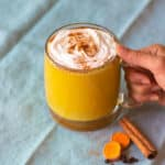 turmeric latte in a cup with whipped cream